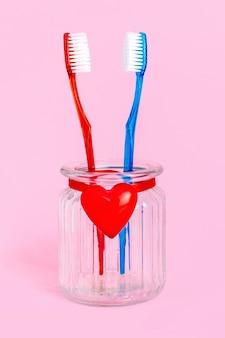 Een paar verliefd op twee tandenborstels in een glas met een rood hart, liefde, relatie, man en vrouw, man en vrouw. valentijnsdag kaart.