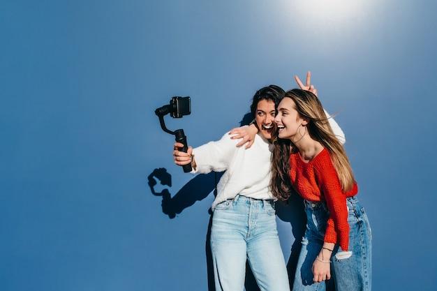 Een paar vrienden, de ene blondine en de andere brunette glimlachend, nemen een video op met hun mobiele telefoons voor een blauwe muur.
