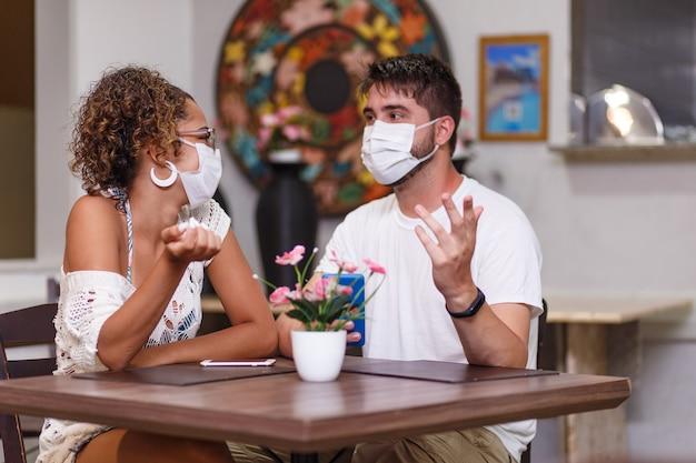Een paar vrienden veiligheid praten zittend op een restaurant in de buitenlucht met een veiligheidsmasker tegen de covid-19 coronavirus pandemie. nieuw normaal leven concept