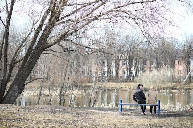 Een paar vrienden zitten in een herfstpark op een bankje