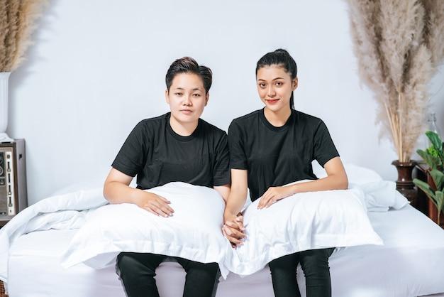 Een paar vrouwen zaten op het bed met kussens om hun benen te ondersteunen.