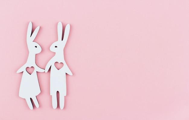 Een paar witte houten konijnen met harten in hun borst op een roze achtergrondexemplaarruimte