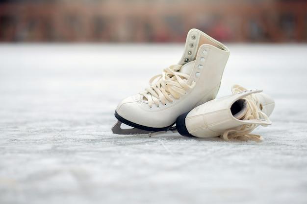 Een paar witte kunstschaatsen liggen op een open ijsbaan