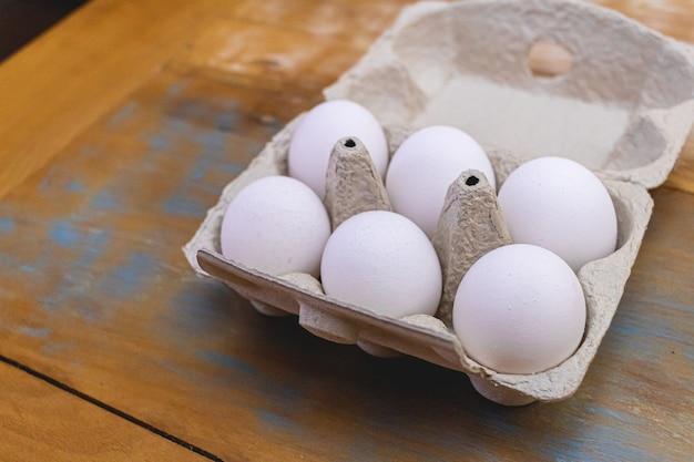 Een paar witte rauwe kippeneieren in een klein dienblad op een houten tafel