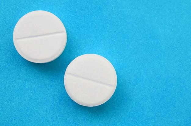 Een paar witte tabletten liggen helderblauw
