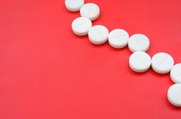 Een paar witte tabletten liggen op een felrood achtergrondoppervlak.