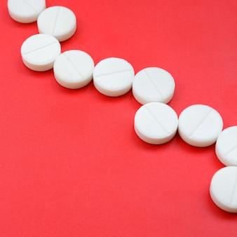 Een paar witte tabletten liggen op een felrood achtergrondoppervlak