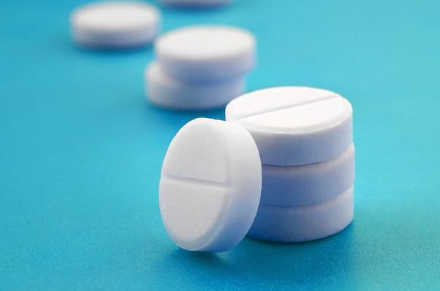 Een paar witte tabletten liggen op een helderblauwe ondergrond.