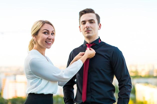 Een paar zakenlieden, aantrekkelijke brunette man en mooie blonde vrouw staan op het dak