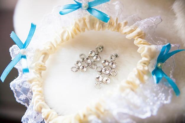 Een paar zilveren oorbellen, witte kousenband met blauwe strikken