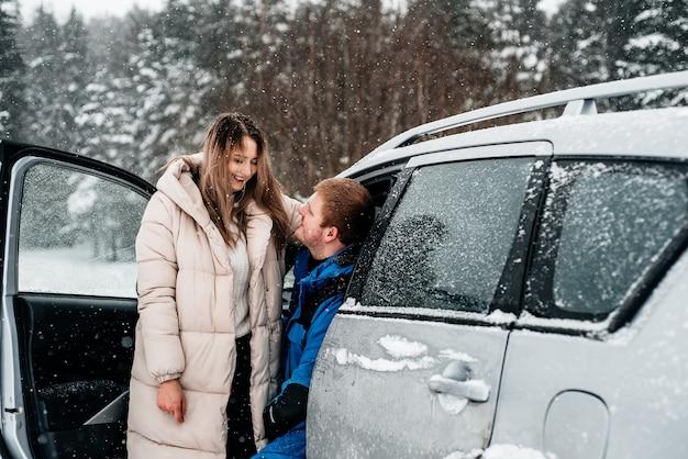 Een paar zit met kopjes achter in een auto en picknick in een sneeuwbos