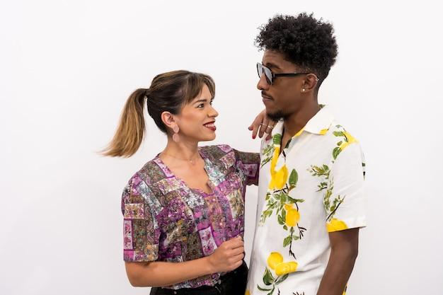 Een paar zwarte jongen en een blank meisje op een witte achtergrond, bloemenhemden