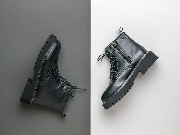 Een paar zwarte leren schoenen met veters op een witte en zwarte ondergrond