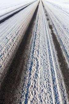 Een paar zwarte sporen van verkeer op sneeuw op een asfaltweg