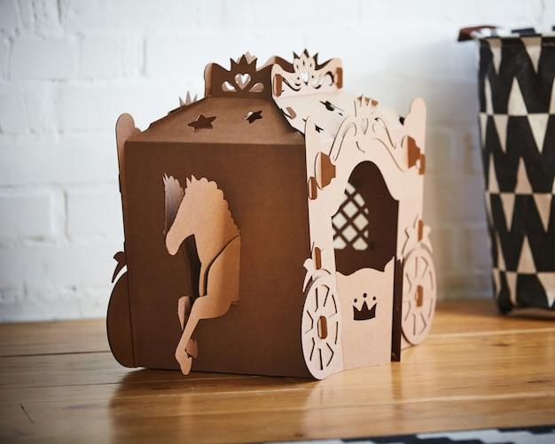 Een paard en een koets van bruin karton, waar het paard de koets aan trekt