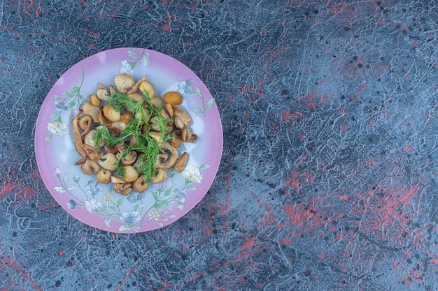 Een paars bord champignons met kruiden.