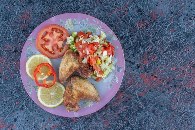 Een paars bord kippenvlees met groentesalade.