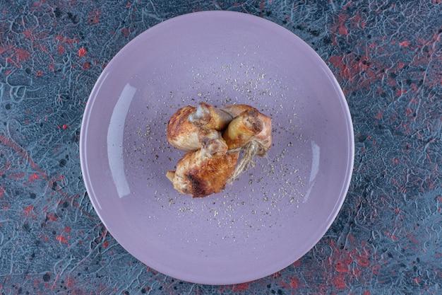 Een paars bord met kippenpoten vlees in touw.