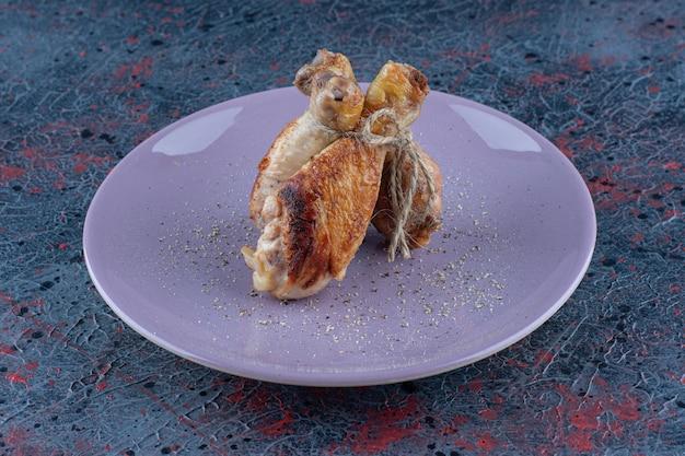 Een paars bord met kippenpoten vlees in touw