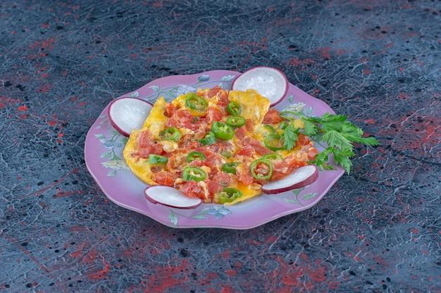 Een paars bord omelet met groenten.