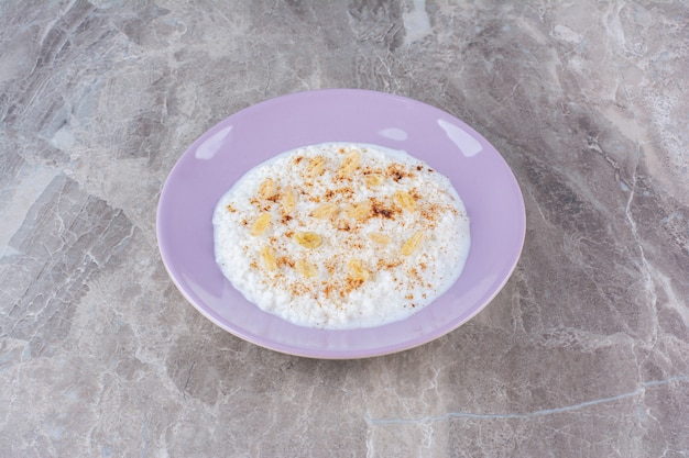 Een paars bord vol gezonde havermoutpap met kaneelpoeder