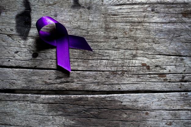 Een paars lint op een donkergrijze rustieke houten oppervlak, geweld tegen vrouwenconcept