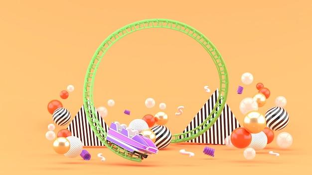 Een paarse achtbaan tussen kleurrijke ballen onn oranje. 3d-weergave.