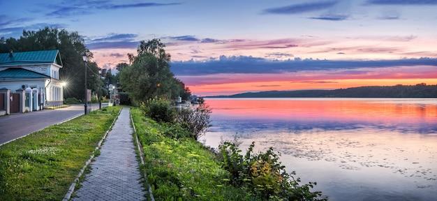 Een pad aan de wolga-dijk in plyos, het levitan museum en de roze kleuren van een zomerse zonsondergang boven de rivier