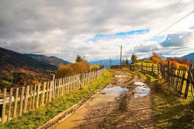 Een pad langs de rand van een heuvel met een grote plas en een oud hek tegen de achtergrond van een kleurrijk bos