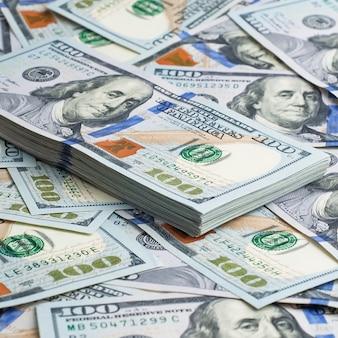 Een pak amerikaanse dollars op de achtergrond van honderd dollarsrekeningen.