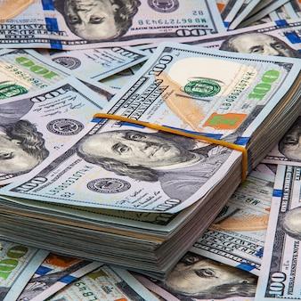 Een pak dollars tegen de ruimte van verspreide biljetten van honderd dollar.