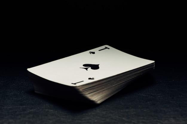 Een pak kaarten op een zwarte achtergrond. schoppen aas.
