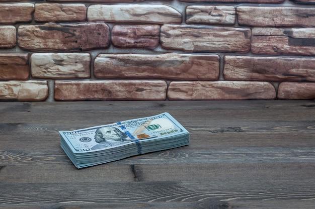 Een pak nieuwe amerikaanse dollars op een tafel in de buurt van een bakstenen muur.