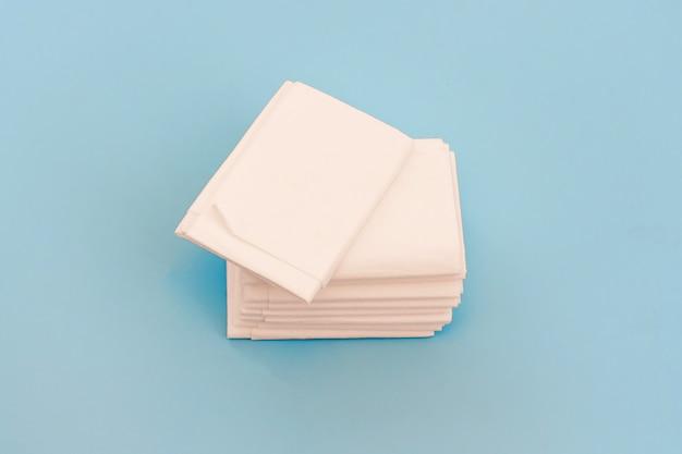 Een pak nieuwe hygiënische witte papieren zakdoekjes of servetten op lichtblauwe achtergrond
