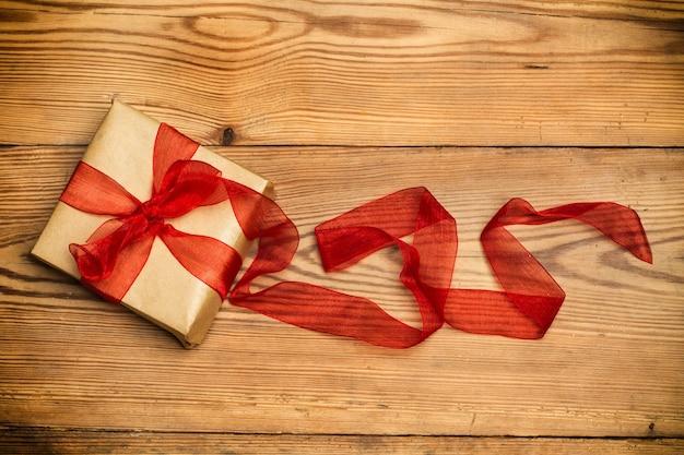 Een pakket met een rode strik op een houten tafel in bovenaanzicht