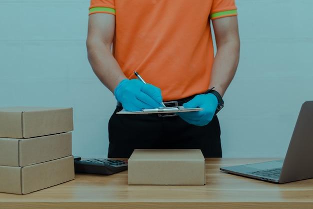 Een pakketbezorger die de pakketdozen telt