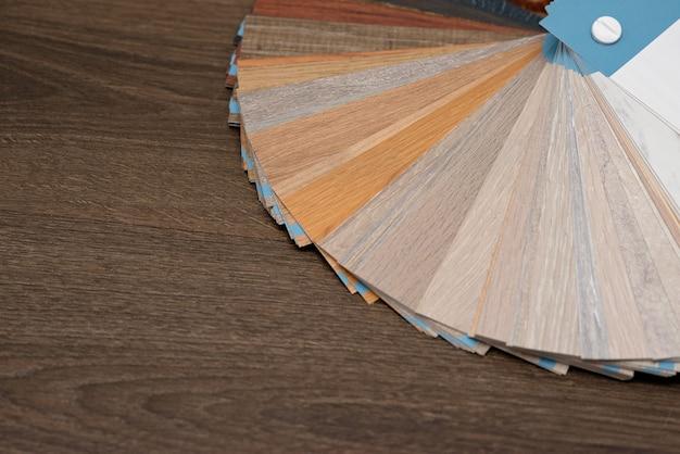 Een palet van texturen en decor voor de houten vloer van het laminaat en vinyl op een donkere houten tafel. interieur ontwerp. een huis plannen en bouwen.