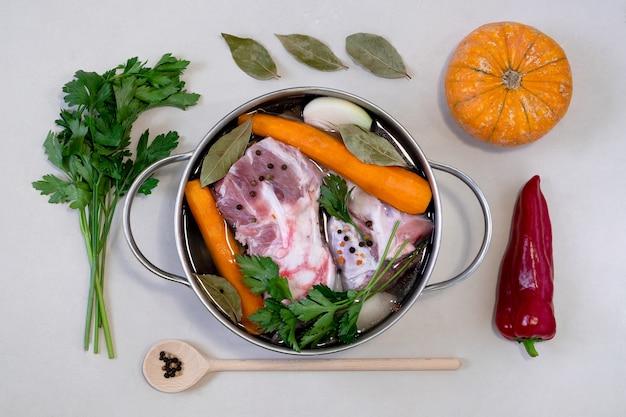 Een pan met vlees en groenten voor het koken van de bouillon en andere ingrediënten op een grijze ondergrond.