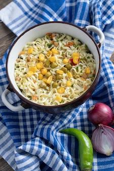 Een pan noedels met groenten op tafellaken