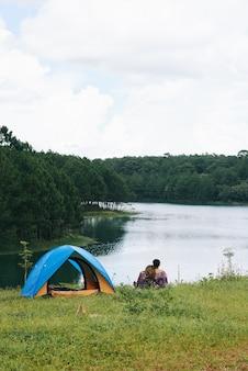 Een panfoto van een paar knuffelen op de rivier bij de tent met hun rug naar de camera