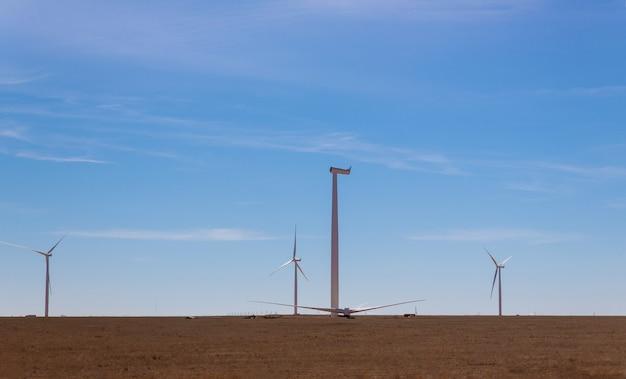 Een panoramisch uitzicht op de windmolen geïnstalleerd in een veld installatie windturbine met blauwe hemel