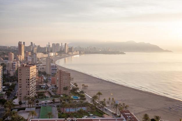 Een panoramisch uitzicht op het strand van benidorm bij zonsopgang