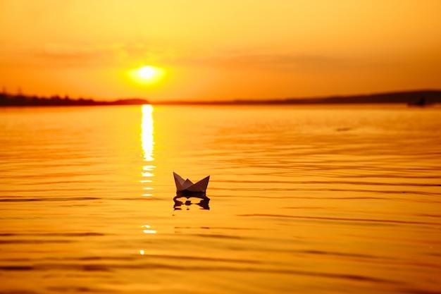 Een papieren bootje drijft weg in de verte. boot op het water. mooie zonsondergang. origami. rivier. meer.