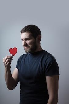 Een papieren hart vasthouden met een pincet en ernaar kijken met walging en negatieve emoties laten zien, denkend aan een vraag, een zeer verward idee