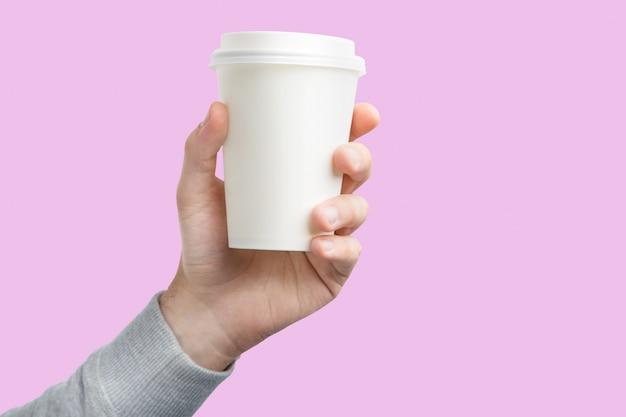 Een papieren kopje koffie in de hand. witboek ter beschikking geïsoleerde kop van koffie