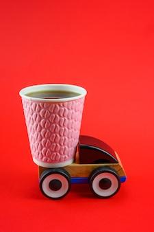 Een papieren kopje koffie rijdt op een speelgoedauto op een rode achtergrond.
