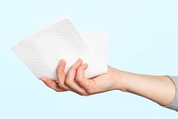 Een papieren servet of keukenrol in de hand van een vrouw. concept van hygiëne