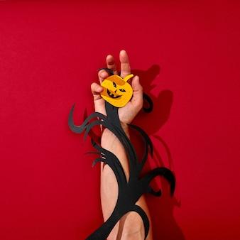 Een papieren tak en een enge lachende pompoen sieren de hand van een man op een prachtige achtergrond met weerspiegeling van schaduwen en kopie ruimte. handwerk als een halloween-lay-out