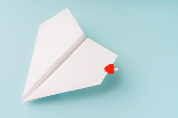 Een papieren vliegtuigje met een hart op een blauwe achtergrond. het concept van een liefdesboodschap.