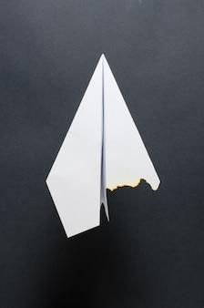 Een papieren vliegtuigje met een verbrande vleugel. donkere achtergrond. het concept van een brand in het vliegtuig of de crash.
